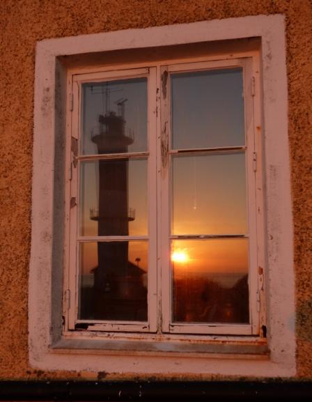 Solnedgången speglas i fyrvaktarbostaden.